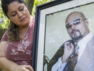 Parkland Health & Hospital System nurse Dolores Diaz poses for a photo with a photo of her late husband on July 9, 2020 at their home in Grand Prairie. Dolores' husband Juan died unexpectedly in late June. (Juan Figueroa / Staff Photographer)