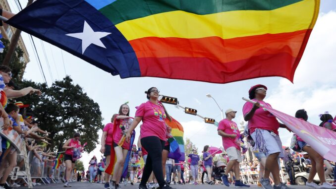 People marching with the Mobilize for Equality group pass by the Texas rainbow flag during the Texas Freedom Parade, Sunday, September 17, 2017. On Monday, June 15, 2020, the U.S. Supreme Court issued a landmark ruling extending employment protections to LGBT workers. (Tom Fox/Staff Photographer)