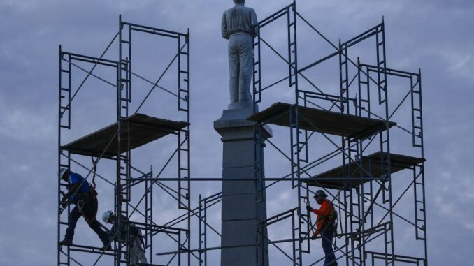 In this June 24, 2020, file photo, construction workers remove the final soldier statue, which sat atop The Confederate War Memorial in downtown Dallas. The Confederate battle flag is losing its place of official prominence in the South 155 years after the end of the Civil War and some Southern localities have removed memorials and statues dedicated to the Confederate cause. (Ryan Michalesko)